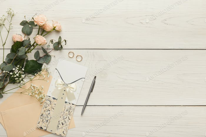 Wedding invitation cards and envelopes on white wooden table, top view