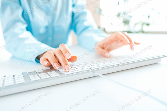 Woman office worker typing on the keyboard