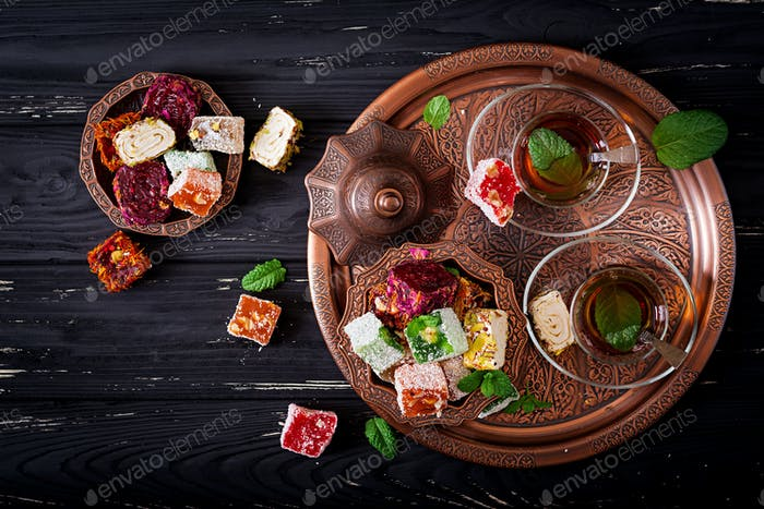 Bowl with various pieces of turkish delight lokum and black tea with mint