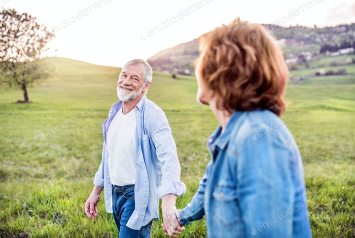 Senior couple walking outside in spring nature, holding hands.