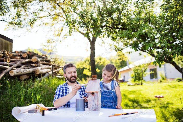 Vater mit einer kleinen Tochter draußen, Malerei Holz Vogelhaus.