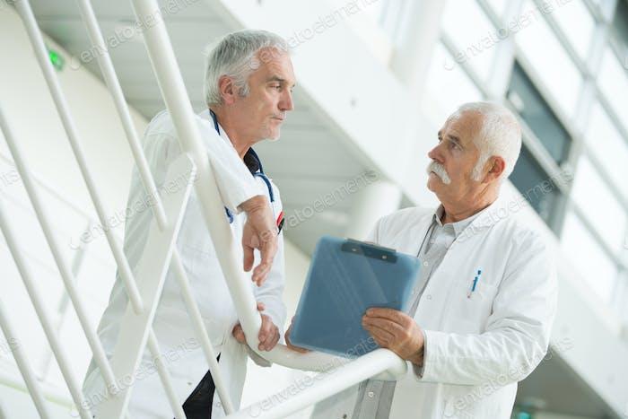 Seniorenarbeiter im Gespräch auf Treppenhaus