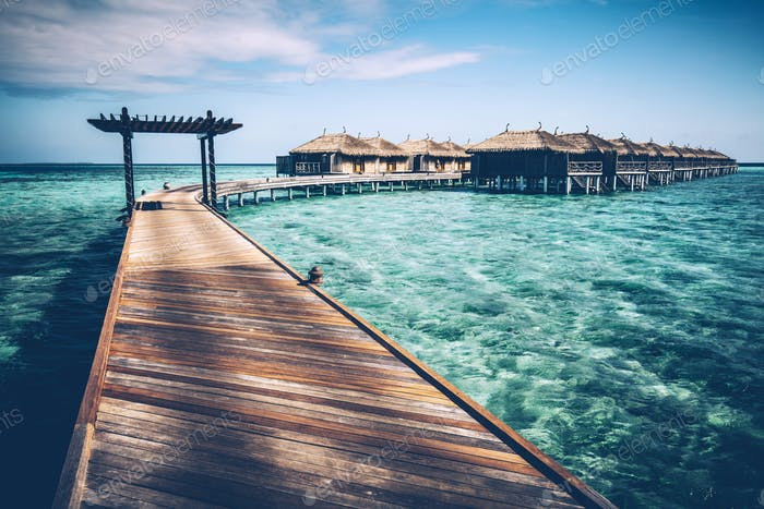 Wooden jetty with arch on a clean turquoise ocean water.