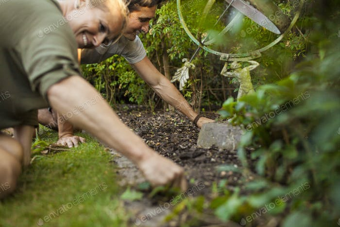 Happy couple gardening together in garden