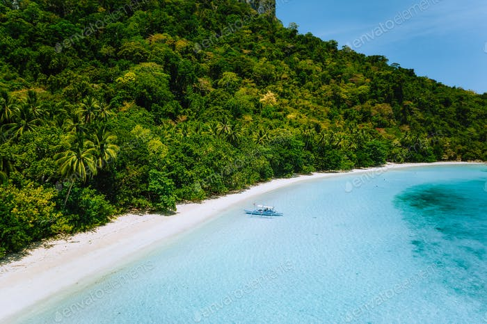 Aerial view of tropical boat moored at secluded white sand beach with turquoise ocean lagoon shallow