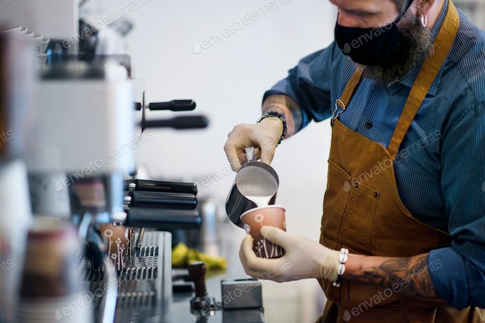 Barista working with gloves, coffee shop open after lockdown quarantine