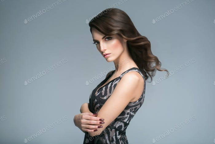 Beautiful woman with curly hairstyle portrait over gray background. Female young beauty model g