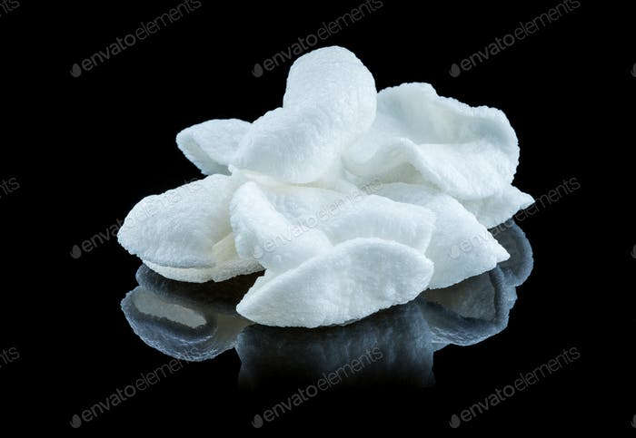 Chips from white rice over black background