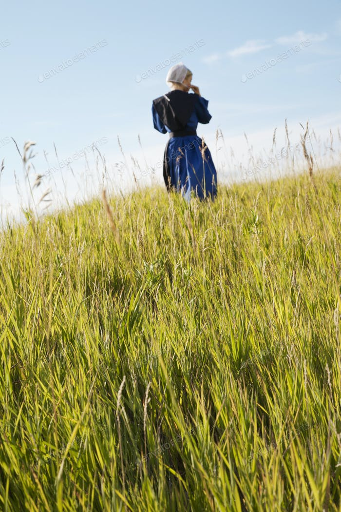 Defocused Old Order Amish Woman Walking in a Field