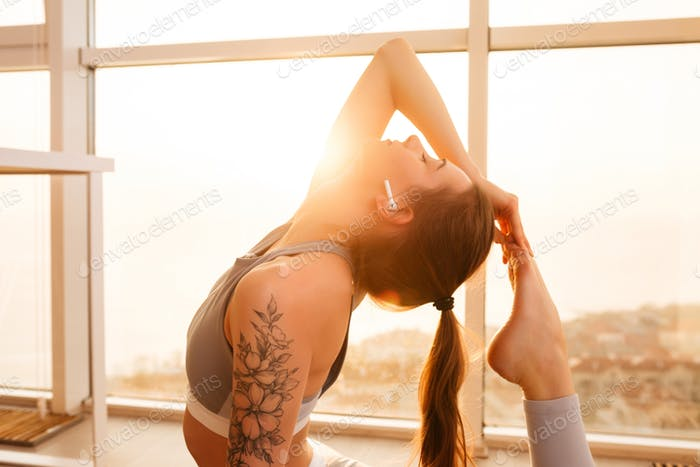 Beautiful lady practicing yoga poses listening music in earphones at home with big beautiful window