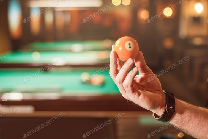 Male hand shows a billiard sphere number eight.