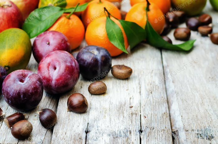 fruit. tangerines, plums, pumpkins, apples and chestnuts