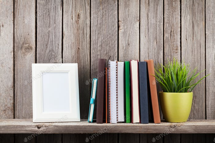 Wooden shelf with photo frames, books and plant