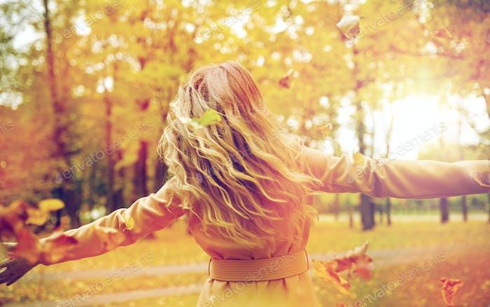 glückliche Frau mit Spaß mit Blättern im Herbst Park