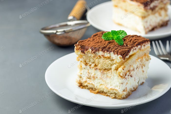 Two piece of traditional italian Tiramisu dessert cake on a whit