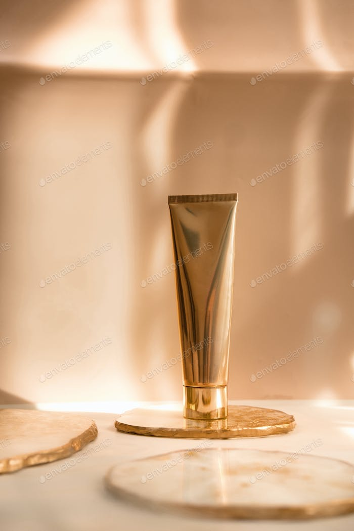 Golden cosmetic tube on pastel color minimalism beauty