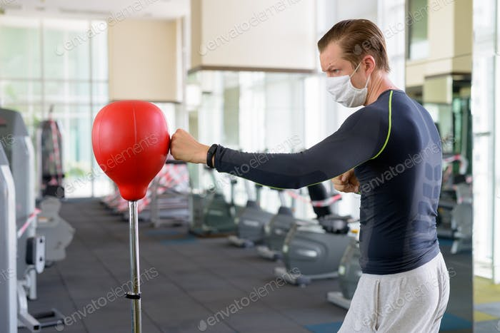 Young man with mask for protection from corona virus outbreak boxing at gym during corona virus