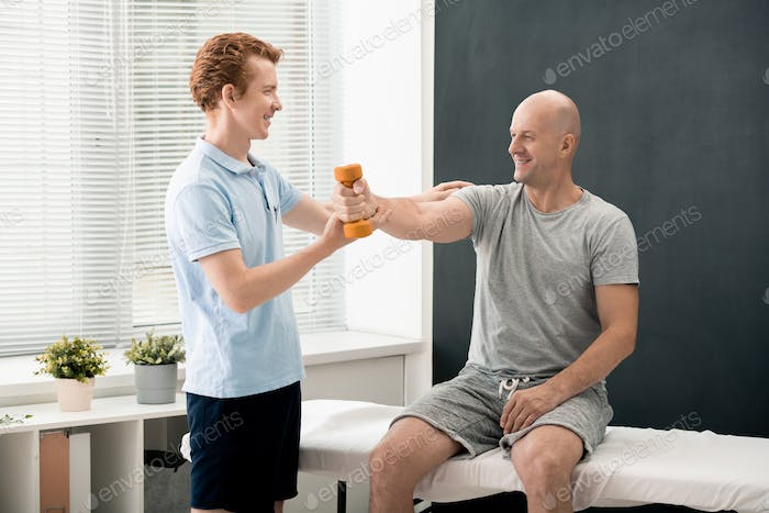 Young smiling physiotherapist helping mature male patient lift and stretch arm