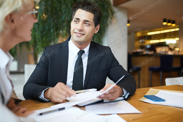 Handsome businessman meeting with business partner in restaurant