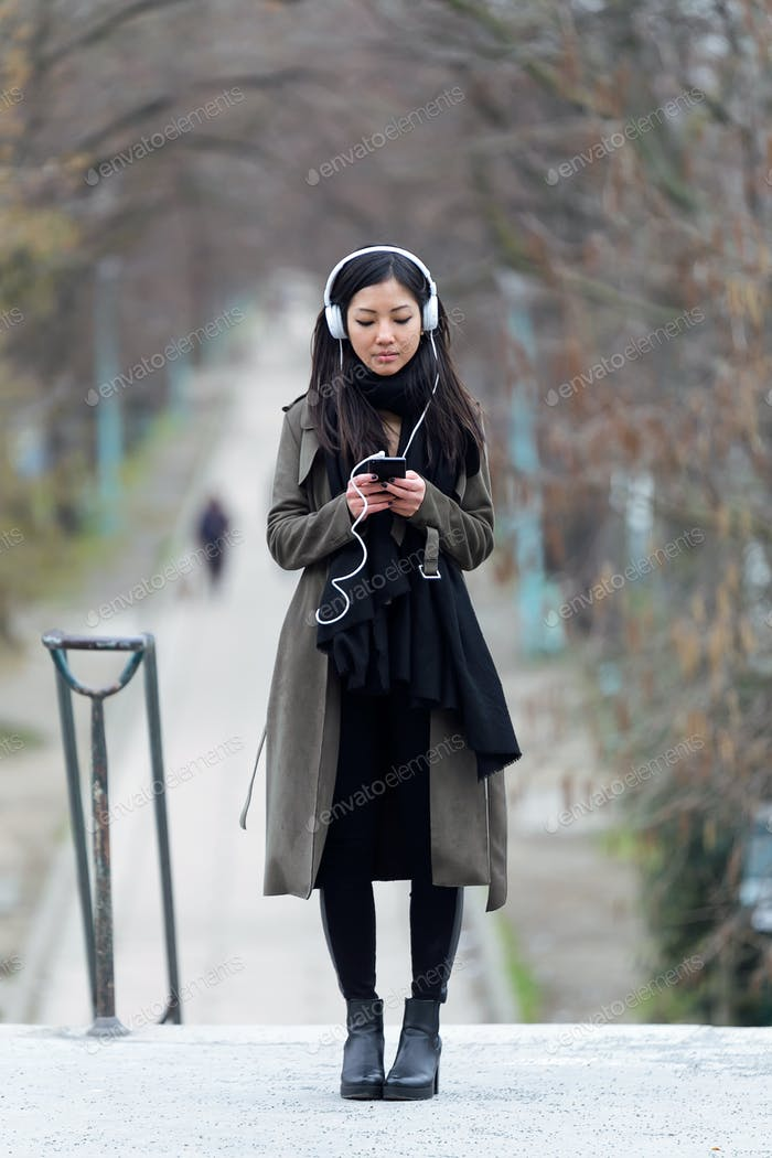 Pretty asian young woman listening to music with her smartphone