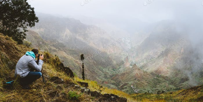 Panoramic shot of traveler making photo of amazing steep mountainous terrain with lush canyon valley
