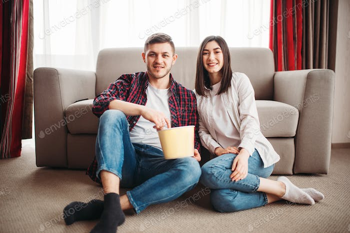 Couple sitting on floor and watch tv with popcorn