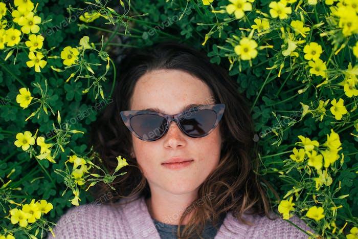 Millennial Frau lag in Blumen im Frühlingsgras