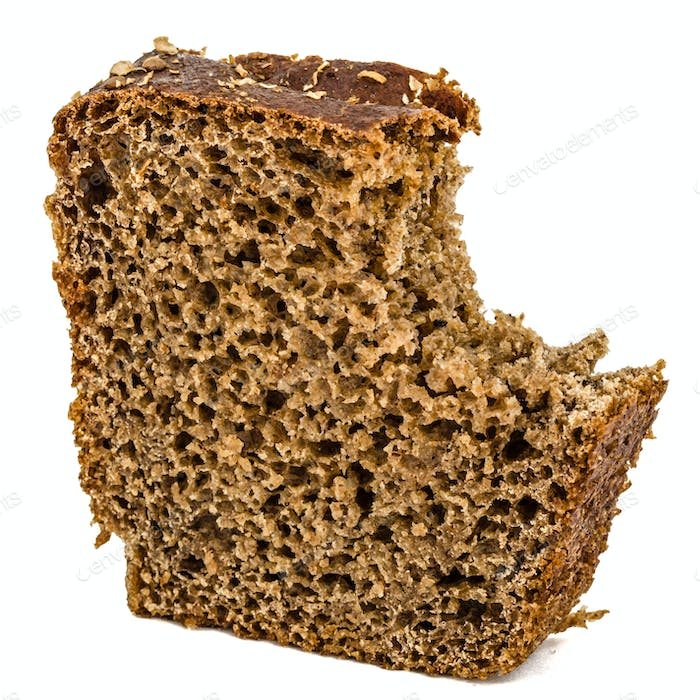 Bitten slice of bread made of dark flour, isolated on white back