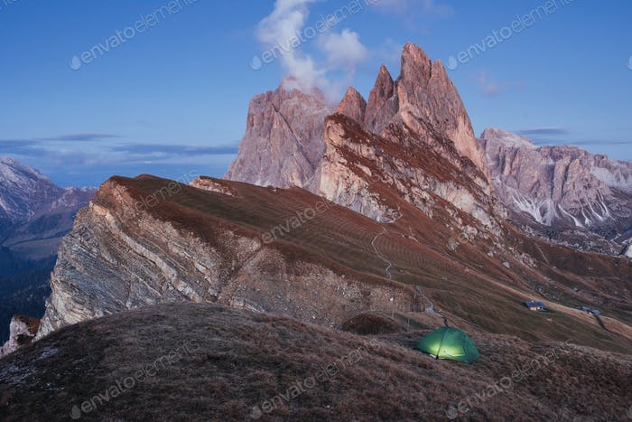 Big cliff. Green tent standing on the hill. Awesome place in the alpes of Seceda