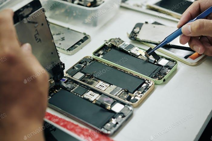 Repairman fixing smartphones