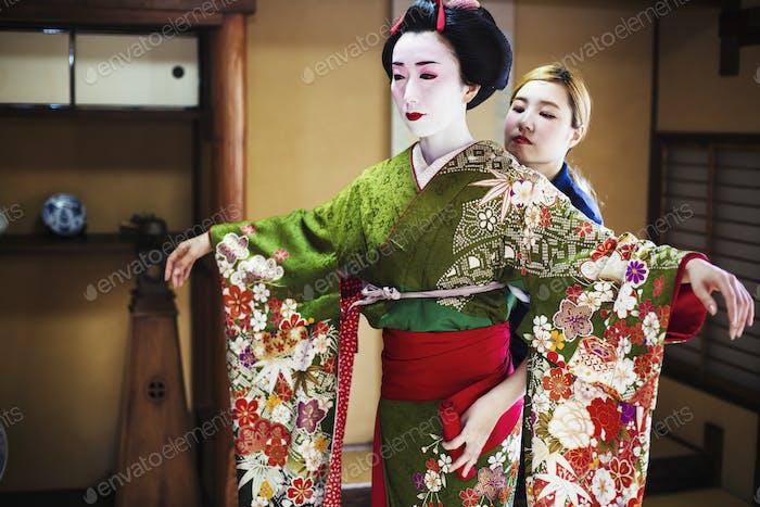 Eine Frau, die im traditionellen Geisha-Stil gekleidet ist, trägt einen Kimono und Obi, mit einem aufwändigen