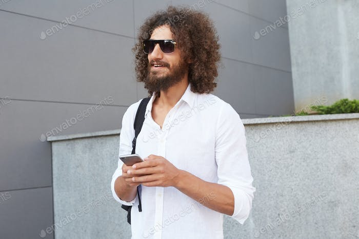 Young good looking curly man with beard standing over city background, holding smartphone