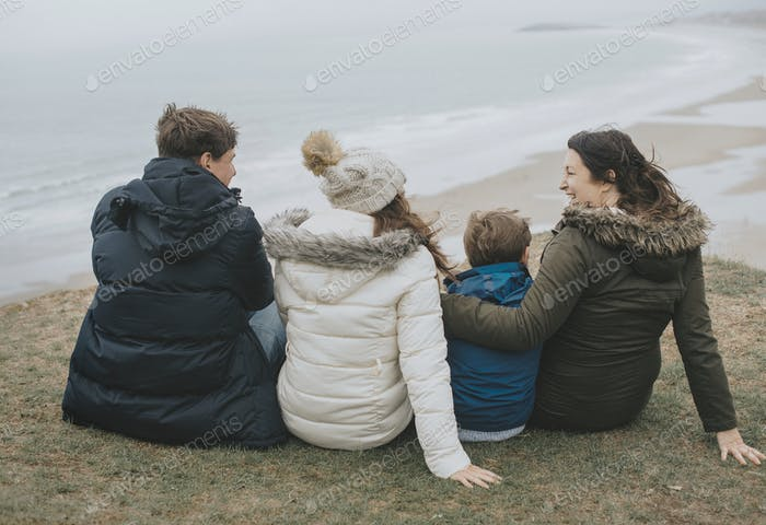 Happy family sitting by the beach
