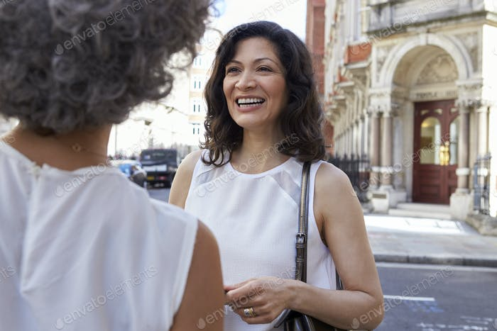 Two female friends talking in the street, close up