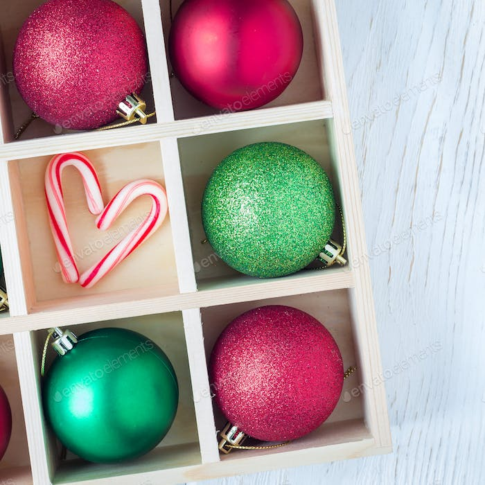 Preparation for Christmas: festive balls and candy cane in wooden box on white table, square
