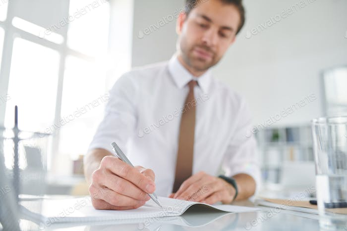 Young busy broker holding pen over blank page of copybook