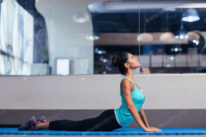 Frau tun Yoga-Übungen im Fitnessstudio
