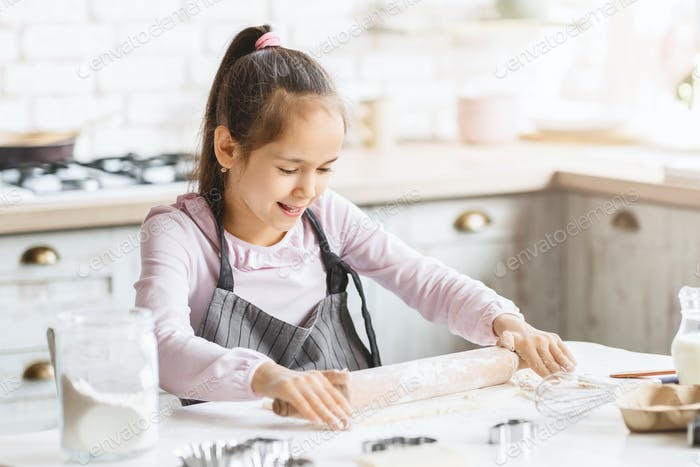 Preteen girl using rolling pin, practicing with dough on kitchen table