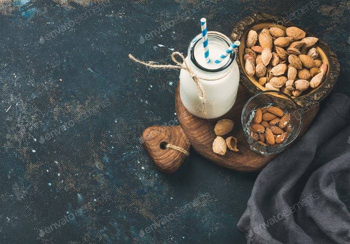 Fresh almond milk in glass bottle with almonds in bowls