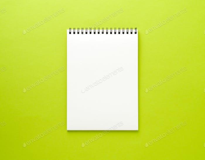 Leere Notizblock weiße Seite auf grünem Schreibtisch, farbiger Hintergrund. Draufsicht, Leerraum für Text.