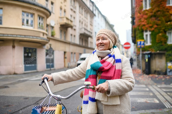 Senior woman with bicycle crossing road outdoors in city.
