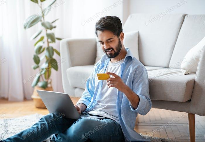 Millennial Arab Guy, der Zahlungen mit Laptop und Kreditkarte zu Hause macht