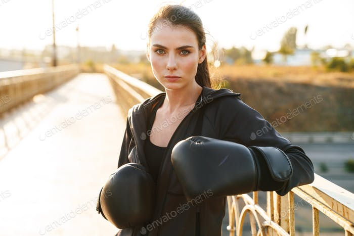 Woman boxer in gloves outdoors.
