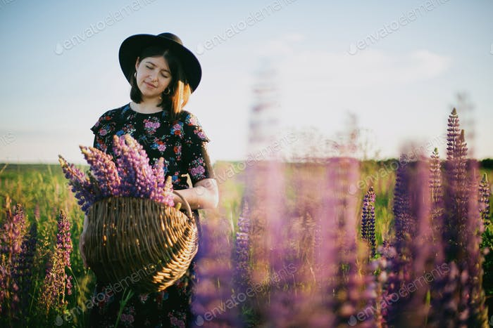 Beautiful woman relaxing in sunny lupine field with rustic basket with flowers. Tranquil moment