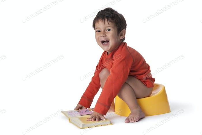 Toddler boy sitting on a potty