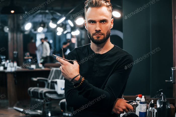Young bearded man standing in barber shop and holding scissors