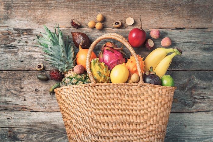 Tropische Früchte in einem Korb auf hölzernem Hintergrund. Draufsicht. Kopierraum. Tropische Früchte flach legen