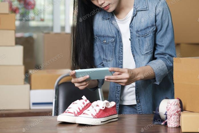 Online seller owner take a photo of product for upload to website online shop.