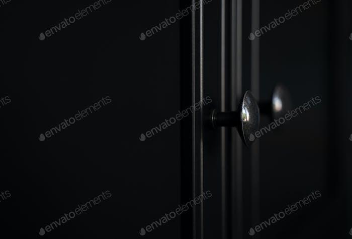 closeup of metallic door knob on black clothes cabinet