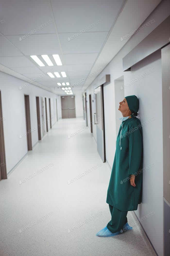 Tensed female surgeon leaning on wall in corridor